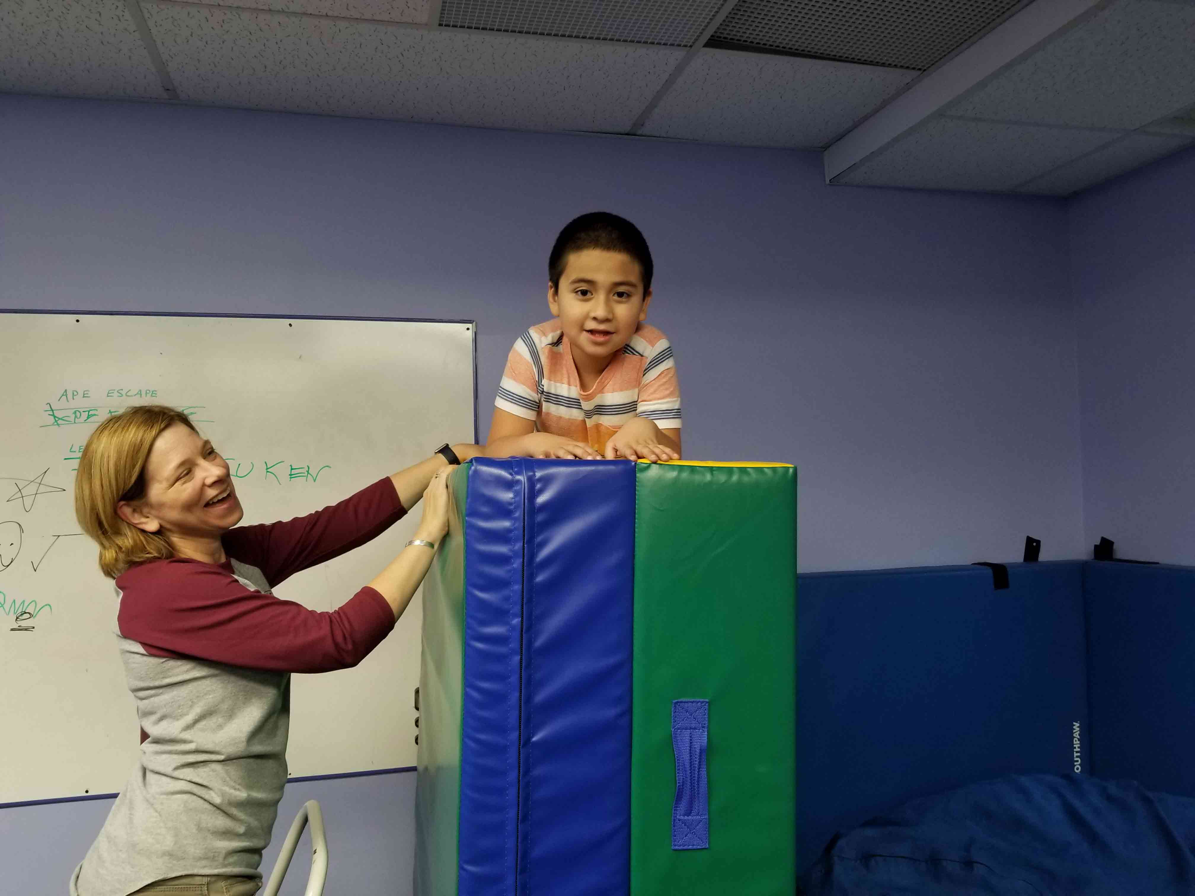Child on top of gym mats with personal instructor