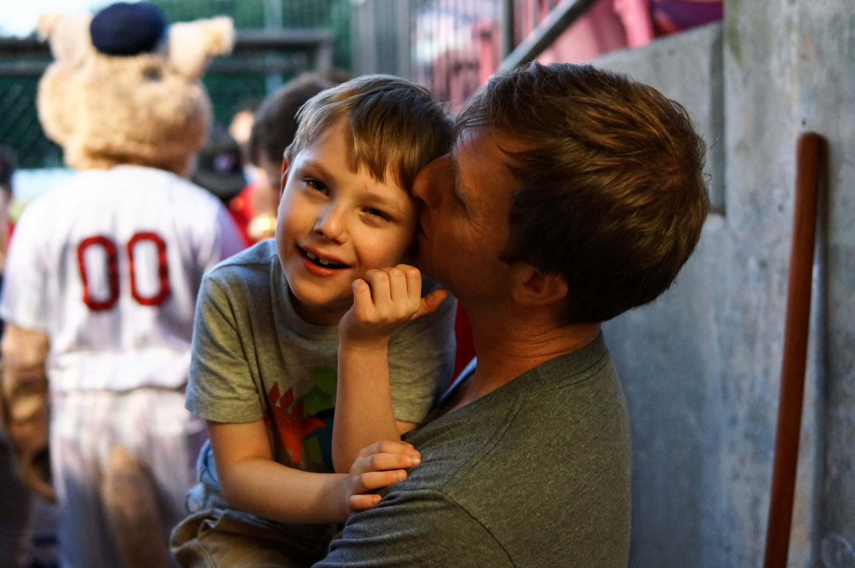 Father kissing son on cheek