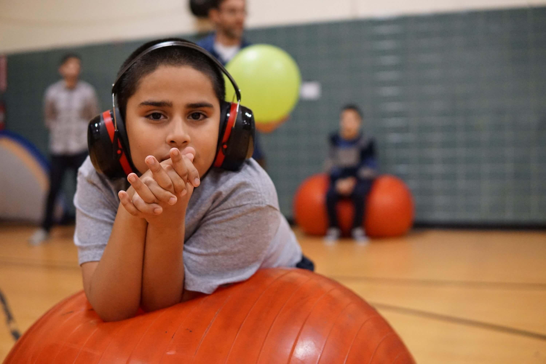 Boy on a big bouncy ball in gym