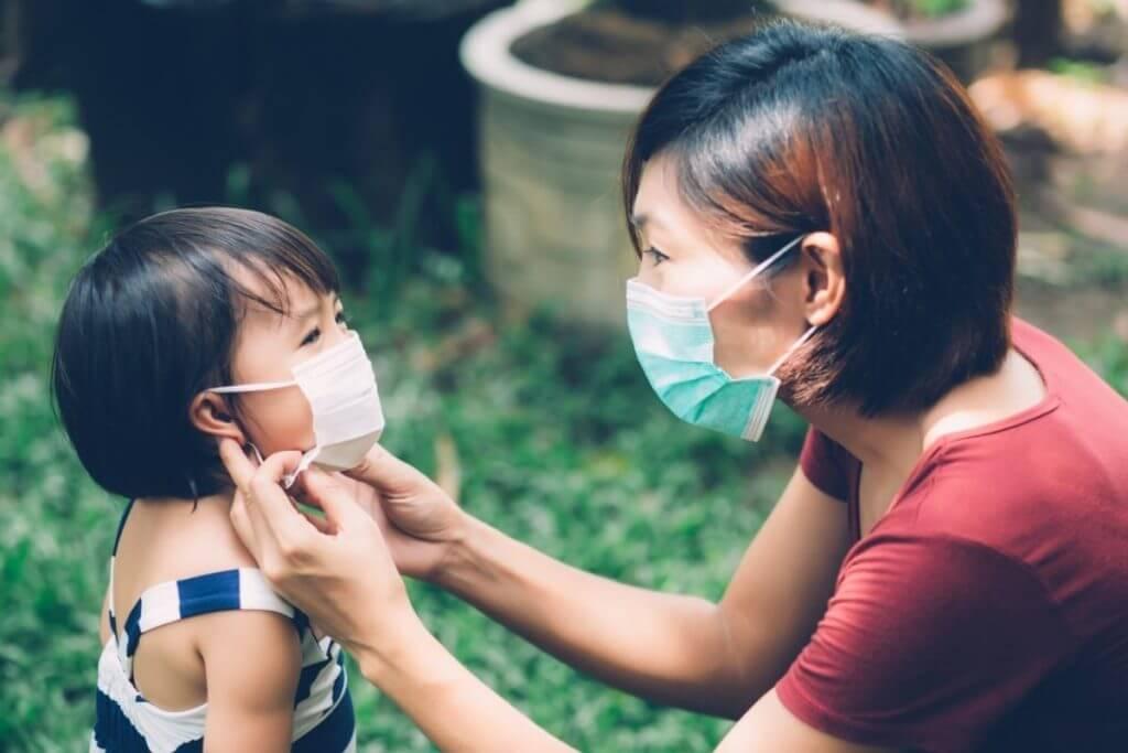 Masked woman putting mask on child